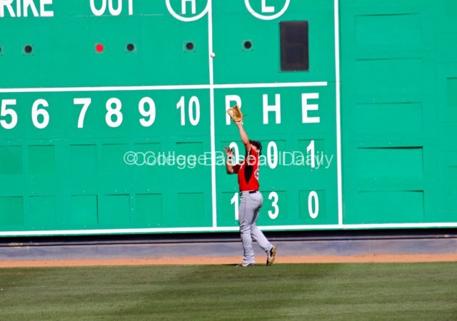 Kyle Ferramola catches a ball on the warning track in front of the scoreboard.