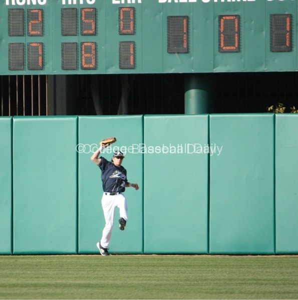 Jared Turocy makes a leaping catch in front of the wall.