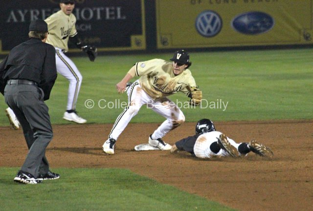 Garrett Hampson dives into second base as Dansby Swanson applies the tag.