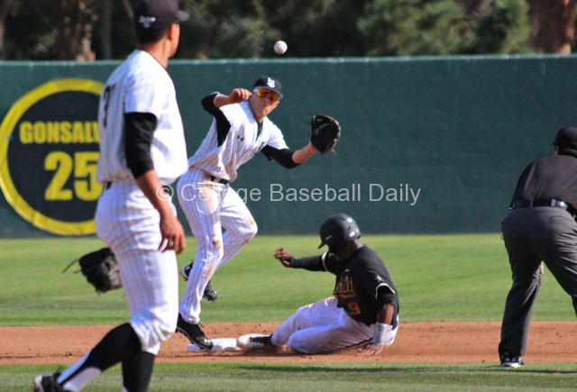 Xavier Turner swipes second under Zack Domingues.