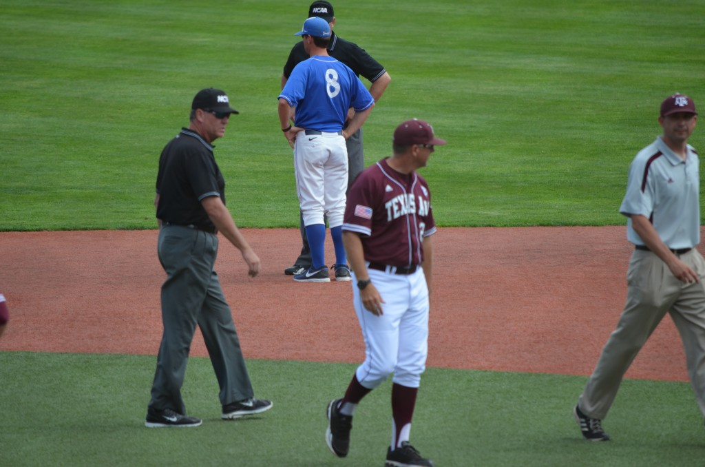 UCSB coach Andrew Checketts (8) requests an explanation of the runner's interference call in the seventh inning that cost the Gauchos two baserunners, while A&M coach Rob Childress leaves the field after checking on his second baseman. (photo by Aaron Yost)